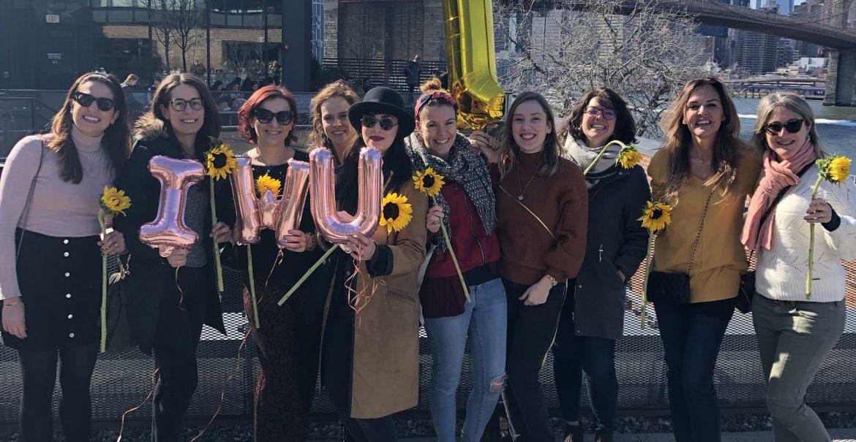 Immagine delle donne di IWUSA si ritrovano a Brooklyn per festeggiare il primo anno della Community, sullo sfondo la skyline di New York e il World Trade Center